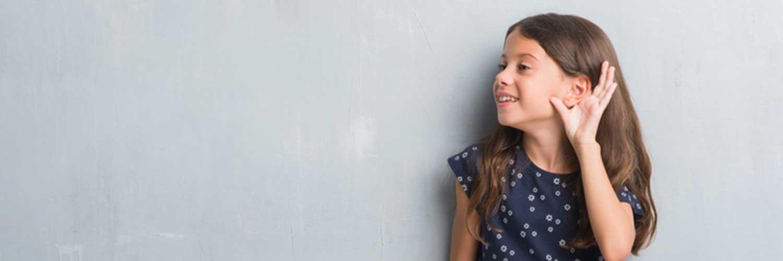 Ein Kind steht vor einer grauen Wand und hält sich die Hand ans Ohr.