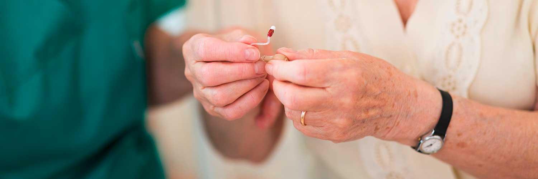 Eine ältere Dame hält ein Hörgerät in der Hand und wird von einer Verkäuferin beraten.