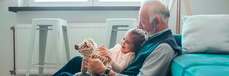 Ein Großvater spielt mit seiner Enkelin und ihrem Plüschtier.