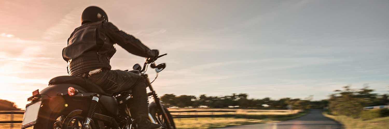 Mann, der bei Sonnenuntergang auf dem Land Motorrad fährt.
