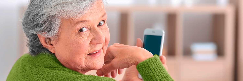 Ältere Dame mit Hörgerät im Ohr, die ihr Smartphone benutzt.