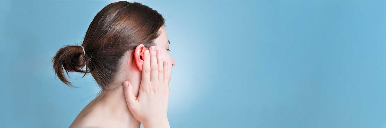 Frau, die sich ihr entzündetes Ohr hält