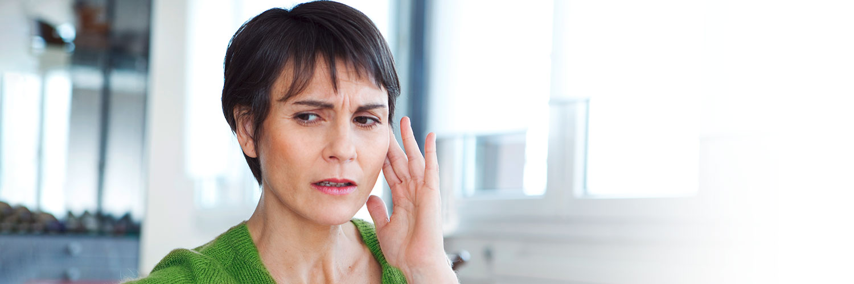 Frau mit kurzen Haaren und grünem Pullover, die sich ihr Ohr hält